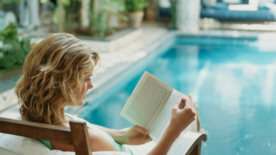teen reading by pool