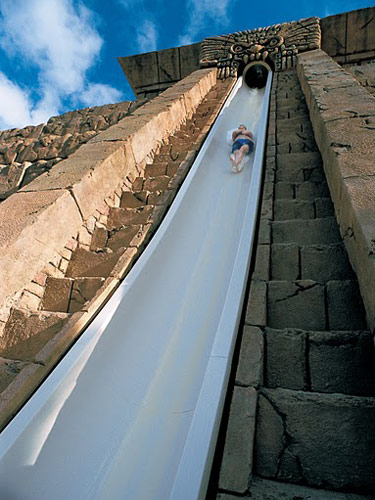 A large slide with a boy going down it