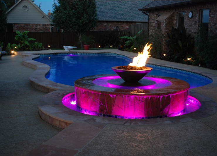 pink lighting on a circular fountain with fire pit