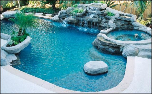 An Oval Shaped Pool With A Waterfall. «